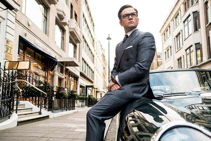 Photo de Taron Egerton dans Kingsman - Le cercle d'or de Matthew Vaughn sur laquelle Taron Egerton est adossé au capot d'une voiture à la manière de James Bond.
