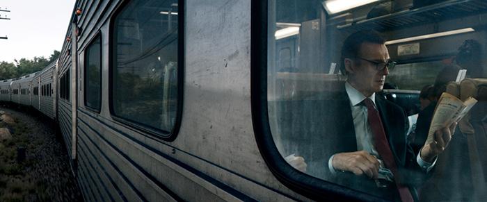 Photo de Liam Neeson lisant son journal dans le train dans The Passenger, le film de Jaume Collet-Serra.