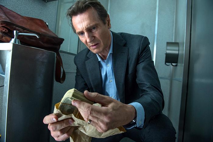 Photo de Liam Neeson tenant une liasse de billets dans le The Passenger de Jaume Collet-Serra.