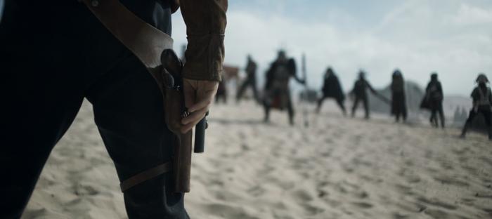 Photo tirée du film Solo : A Star Wars Story, qui est un gros plan sur la jambe de Han Solo, prêt à dégainer son pistolet laser lors d'un duel final.