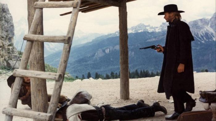 Photo tirée du Spécialiste de Sergio Corbucci, sur laquelle Johnny Hallyday sort d'une maison, armé, avec devant lui deux de ses ennemis au sol.
