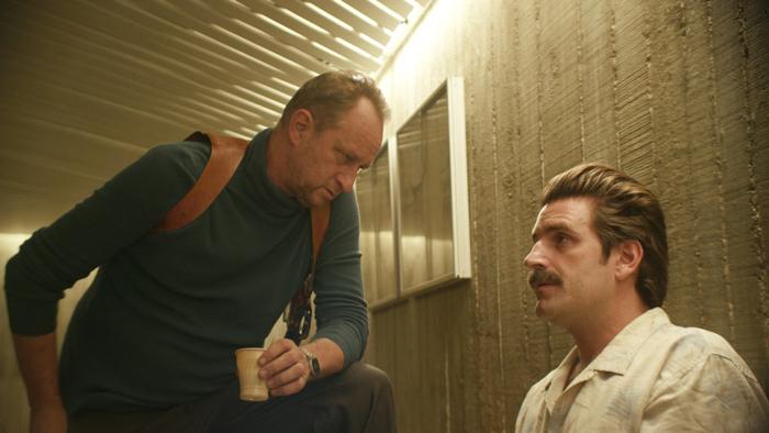 Photo tirée du film Au Poste de Quentin Dupieux sur laquelle Benoît Poelvoorde se penche vers Grégoire Ludig le suspect qu'il interroge dans son commissariat.