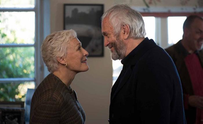"""Photo tirée du film """"The Wife"""" sur laquelle Glenn Close et Jonathan Pryce apparaissent tous deux de profil, alors qu'ils s'adressent tous deux un sourire."""