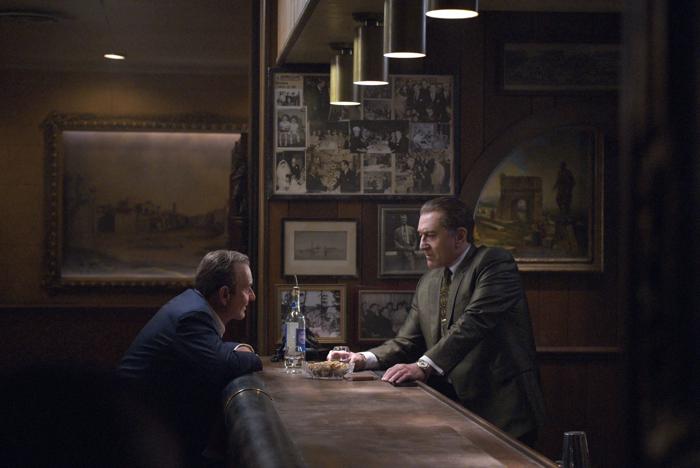 """Photo tirée de """"The Irishman """" de Martin Scorsese, sur laquelle Joe Pesci et Robert De Niro sont face à face sur une table de bar, et parlent en buvant un verre."""