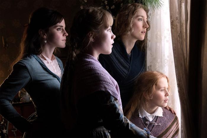Photo tirée de Les Filles du Docteur March de Greta Gerwig, sur laquelle Meg, Amy, Jo et Beth se trouvent côte à côte devant une fenêtre, et regardent avec attention et curiosité vers l'extérieur.