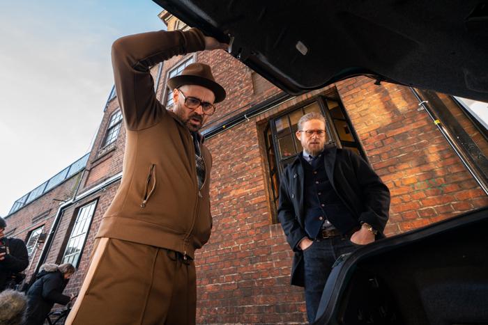 Photo tirée de The Gentlemen de Guy Ritchie, sur laquelle Colin Farrell et Charlie Hunnam regardent tous les deux à l'intérieur du coffre d'une voiture avec un air étonné.