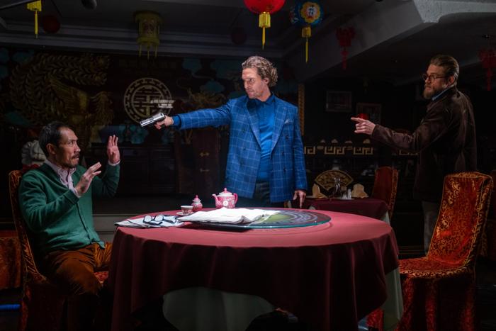 Photo tirée du film The Gentlemen, sur laquelle Matthew McConaughey pointe une arme sur un mafieux assis à la table d'un restaurant, pendant que Charlie Hunnam lui parle.