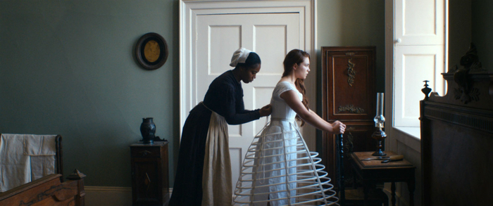 Photo tirée du film The Young Lady, sur laquelle Naomie Ackie noue le corset de Florence Pugh.