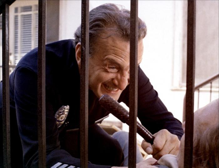 """Photo tirée du film """"Les Flics ne dorment pas la nuit"""", sur laquelle le policier interprété par George C. Scott explose et menace avec une matraque un propriétaire malhonnête."""